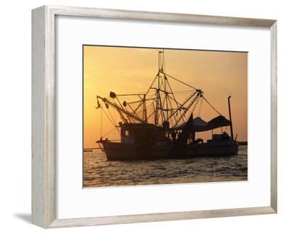 A Shrimp Boat Silhouetted against an Orange Sky--Framed Photographic Print