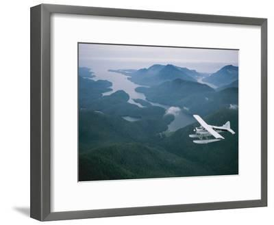 A Beaver Airplane on Floats Flies over Islands and Snowy Mountains-Joel Sartore-Framed Photographic Print
