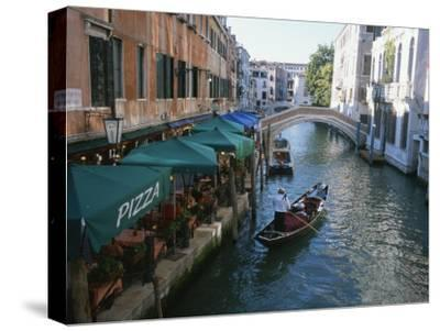 A Gondolier Passes a Restaurant on a Canal in Venice, Italy-Taylor S^ Kennedy-Stretched Canvas Print