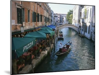 A Gondolier Passes a Restaurant on a Canal in Venice, Italy-Taylor S^ Kennedy-Mounted Photographic Print