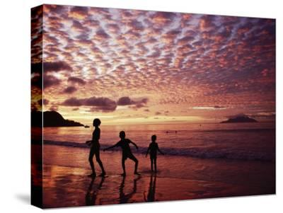 Sunset Reddens a Cloudy Sky as Silhouetted Children Play on the Beach-Steve Raymer-Stretched Canvas Print