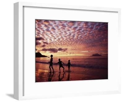 Sunset Reddens a Cloudy Sky as Silhouetted Children Play on the Beach-Steve Raymer-Framed Photographic Print