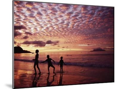 Sunset Reddens a Cloudy Sky as Silhouetted Children Play on the Beach-Steve Raymer-Mounted Photographic Print