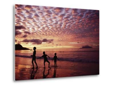 Sunset Reddens a Cloudy Sky as Silhouetted Children Play on the Beach-Steve Raymer-Metal Print