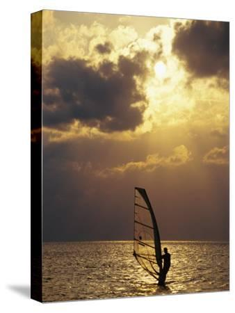 A Windsurfer Skims the Water, Silhouetted by Evening Sun on Pamlico Sound-Stephen St^ John-Stretched Canvas Print