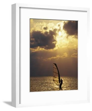 A Windsurfer Skims the Water, Silhouetted by Evening Sun on Pamlico Sound-Stephen St^ John-Framed Photographic Print