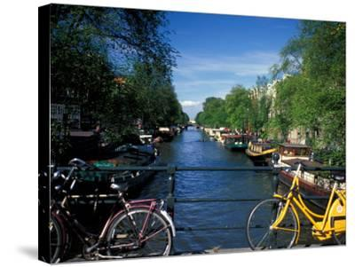 Yellow Bicycle and Canal, Amsterdam, Netherlands-Nik Wheeler-Stretched Canvas Print