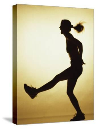 Silhouette of a Young Woman Exercising--Stretched Canvas Print