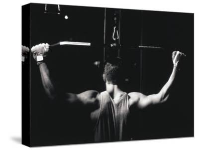 Rear View of a Young Man Exercise on a Lateral Pull-Down Weight Machine--Stretched Canvas Print