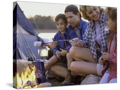 Parents And Their Children Sitting Around a Campfire Toasting Marshmallows--Stretched Canvas Print