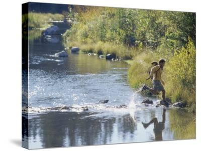 Side Profile of a View of a Young Man Running Across a River--Stretched Canvas Print