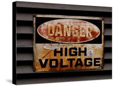 Close-up of a Faded Red and Black and White High Voltage Sign--Stretched Canvas Print
