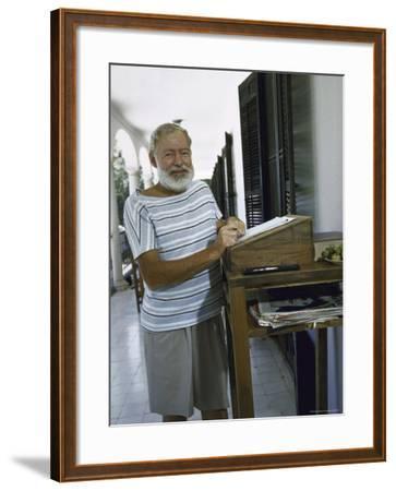 Ernest Hemingway at the Standing Desk on the Balcony of Bill Davis's Home Near Malaga-Loomis Dean-Framed Premium Photographic Print