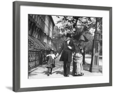 Incredibly Well Dressed Man, Woman and Child Walking by Perfect Brownstone Apartment Buildings-George B. Brainerd-Framed Photographic Print