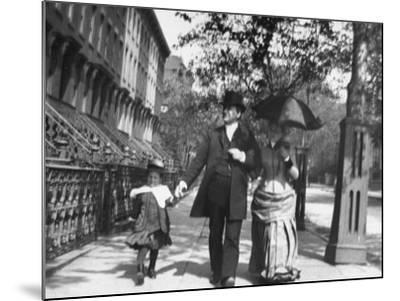 Incredibly Well Dressed Man, Woman and Child Walking by Perfect Brownstone Apartment Buildings-George B. Brainerd-Mounted Photographic Print