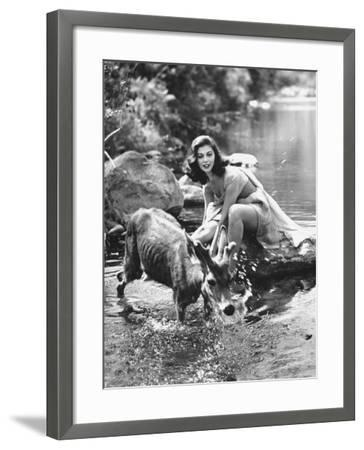 Actress Pier Angeli, Clad in Strapless Chiffon Party Dress Sitting on a Rock in a Pond-Allan Grant-Framed Premium Photographic Print