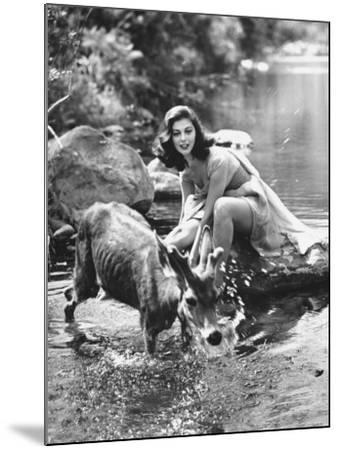 Actress Pier Angeli, Clad in Strapless Chiffon Party Dress Sitting on a Rock in a Pond-Allan Grant-Mounted Premium Photographic Print