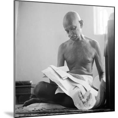 Indian Leader Mohandas Gandhi Reading as He Sits Cross Legged on Floor, at Home-Margaret Bourke-White-Mounted Premium Photographic Print