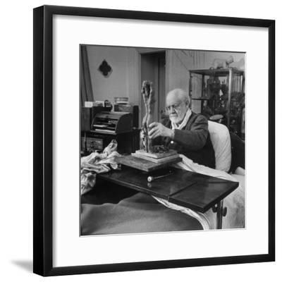 Henri Matisse Sculpting Nude Female Figure While Sitting in Bed in His Apartment-Dmitri Kessel-Framed Premium Photographic Print