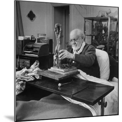 Henri Matisse Sculpting Nude Female Figure While Sitting in Bed in His Apartment-Dmitri Kessel-Mounted Premium Photographic Print