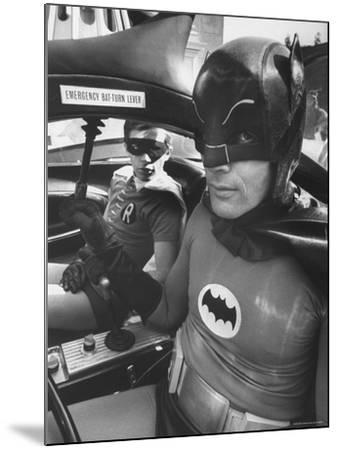 "Batman Adam West and ""Robin"" Burt Ward in Bat Mobile, on Set During Shooting of Scene-Yale Joel-Mounted Premium Photographic Print"