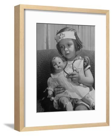 Evelyn Mott playing Nurse with doll as parents adjust children to abnormal conditions in wartime-Alfred Eisenstaedt-Framed Photographic Print