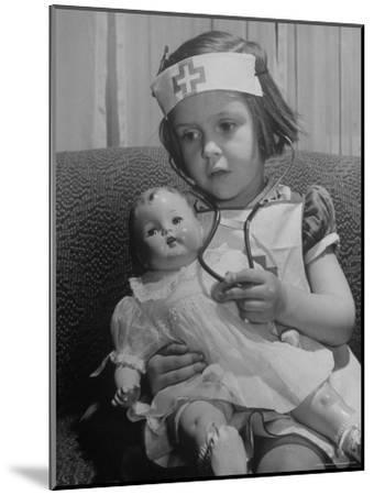 Evelyn Mott playing Nurse with doll as parents adjust children to abnormal conditions in wartime-Alfred Eisenstaedt-Mounted Photographic Print