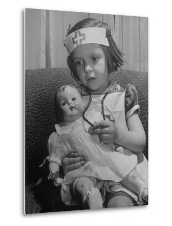 Evelyn Mott playing Nurse with doll as parents adjust children to abnormal conditions in wartime-Alfred Eisenstaedt-Metal Print