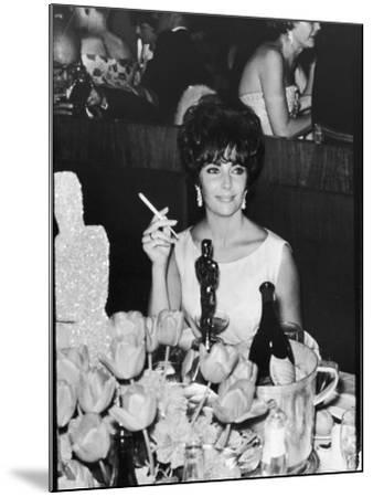 Actress Elizabeth Taylor at Hollywood Party After Winning Oscar, Which is on Table in Front of Her-Allan Grant-Mounted Premium Photographic Print