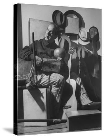 Brazilian Composer Heitor Villa Lobos Playing Native Brazilian Folk Instrument from His Collection--Stretched Canvas Print
