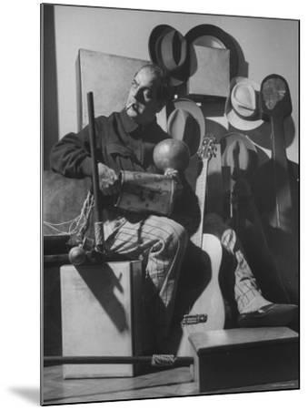 Brazilian Composer Heitor Villa Lobos Playing Native Brazilian Folk Instrument from His Collection--Mounted Premium Photographic Print