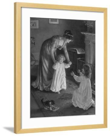Mother with Daughters in Nightgowns, Helping Younger One Take Her First Steps--Framed Photographic Print