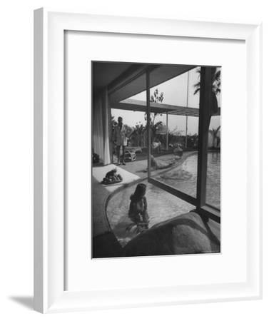 Designer Raymond Loewy Relaxing by Swimming Pool Which Runs from Outdoors Into Living Room-Peter Stackpole-Framed Premium Photographic Print