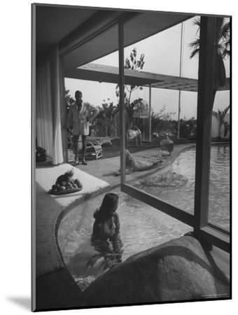 Designer Raymond Loewy Relaxing by Swimming Pool Which Runs from Outdoors Into Living Room-Peter Stackpole-Mounted Premium Photographic Print