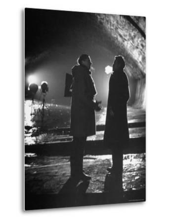 """Carol Reed Coaching Orson Welles as They Stand Against Floodlights During Filming """"The Third Man.""""-William Sumits-Metal Print"""