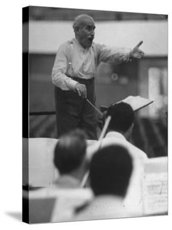 Conductor Arturo Toscanini, Singing and Shouting Instructions While Rehearsing His Men in a Gym-Joe Scherschel-Stretched Canvas Print