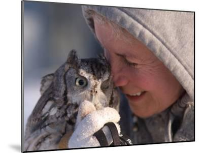 A Woman Holds an Endangered Eastern Screech Owl at a Recovery Center-Joel Sartore-Mounted Photographic Print