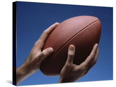 Hands Holding Football with Blue Background--Stretched Canvas Print