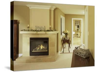 A Fire in the Fireplace and Candles on the Mantle--Stretched Canvas Print