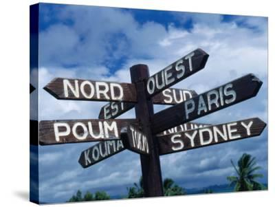 Sign Showing Directions to Other Cities in World, Koumac, New Caledonia-Jean-Bernard Carillet-Stretched Canvas Print