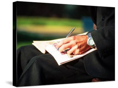 Businessman Writing on Newspaper-Stephen Umahtete-Stretched Canvas Print
