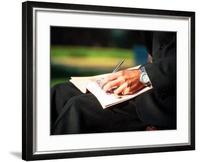 Businessman Writing on Newspaper-Stephen Umahtete-Framed Premium Photographic Print