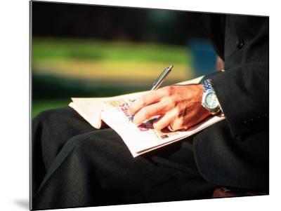 Businessman Writing on Newspaper-Stephen Umahtete-Mounted Premium Photographic Print