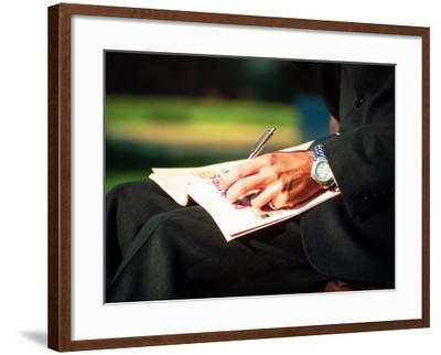 Businessman Writing on Newspaper-Stephen Umahtete-Framed Photographic Print