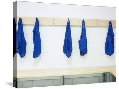 Five Blue Shirts Hanging in Changing Room of Gym--Stretched Canvas Print