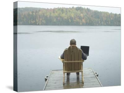 Man Sitting on a Dock Working on Laptop--Stretched Canvas Print