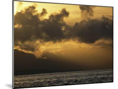 Twilight View of Backlit Clouds over Silhouetted Hills and Calm Water-Tim Laman-Mounted Photographic Print