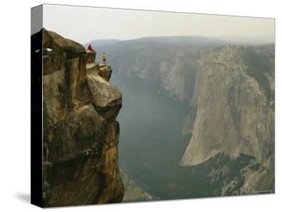 Two Climbers Take in the View of Yosemite Valley from Taft Point-Bill Hatcher-Stretched Canvas Print