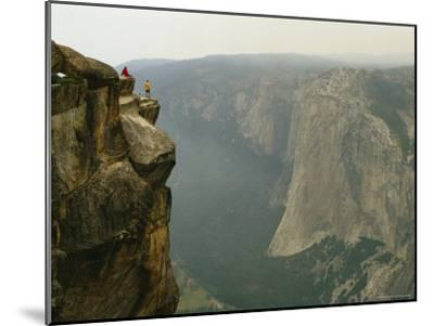 Two Climbers Take in the View of Yosemite Valley from Taft Point-Bill Hatcher-Mounted Photographic Print