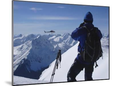 A Back-Country Skier Watches a Heli-Ski Chopper Approach a Peak-Skip Brown-Mounted Photographic Print